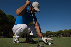 Man's hand putting golf ball in hole Stock Image