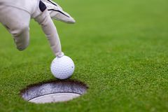 Man's hand putting a golf ball into hole on the Royalty Free Stock Photography