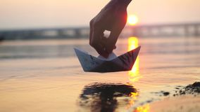 Man`s hand putting paper boat on the water during beautiful sunset with reflection sun in the sea. Man`s hand putting paper boat on the water and pushing it away Stock Photo
