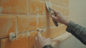 Man`s hand putting seams of orange tiles on the wall stock video footage