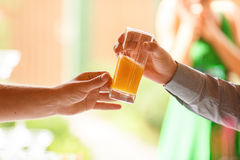 Man's hand reach out a glass with fresh juice to another man.  Royalty Free Stock Images