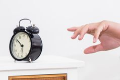 Man hand is reaching out to alarm clock waking up in early morning. Man`s hand is reaching out to alarm clock waking up in early morning Royalty Free Stock Photo