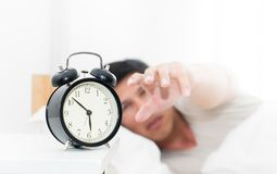 Man`s hand reaching out to alarm clock waking up in early mor. Man`s hand is reaching out to alarm clock waking up in early morning Stock Photography