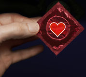 Man's hand with a red condom pack and heart symbol on it Stock Photos
