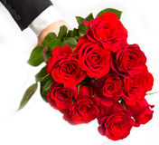 Man's hand with red roses bouquet. A man's hand with red roses bouquet Royalty Free Stock Images