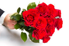 Man's hand with red roses bouquet. A man's hand with red roses bouquet Royalty Free Stock Photos