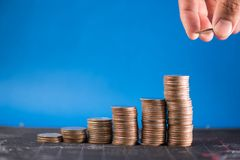 Man`s hand release the coin into the stack illustrate the Finan. Cial saving cocept Stock Photography