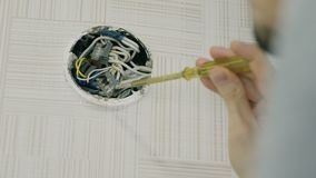 Man`s hand repairing the wires with screwdriver. Looking for burnt wires in electrical junction box.  stock video
