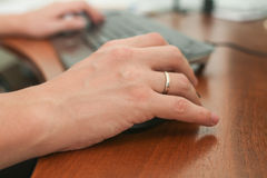 Man's hand with ring on mouse and computer keyboard Stock Photo
