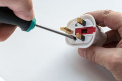 Man's Hand and Screwdriver Fixing Electric Plug. White male hand using a screwdriver fixes a screw into a domestic electrical plug. White background with copy Stock Photo