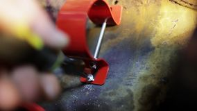 Man`s hand is screwing new red stainless handle to metallic surface. Close-up view of man`s hand professional screwing of small new red stainless handle to stock footage