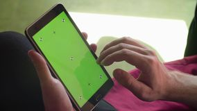Man`s hand scrolling a tablet with green screen Stock Photo