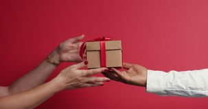 Man`s hand in shirt reach out agift box and woman`s hand take it. On red background stock video