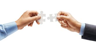 Man`s hand in shirt and man`s hand in suit trying to connect puzzle pieces isolated on white background. Close up. High resolution product stock photo