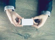 Man`s hand showing business card - closeup shot on dark wooden background.  Stock Photos
