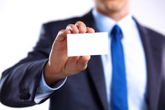 Man's hand showing business card - closeup shot on grey background Royalty Free Stock Photo