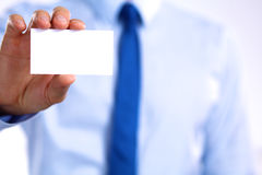 Man's hand showing business card - closeup shot on grey background Stock Photo