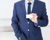 Man`s hand showing business card - closeup shot in office, blank, top view royalty free stock photo
