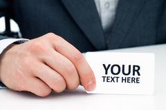 Man's hand showing business card. Royalty Free Stock Image