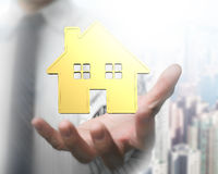 Man`s hand showing golden house. With city buildings background royalty free stock photos