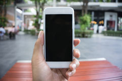 Man's hand shows mobile smartphone in vertical position Royalty Free Stock Image