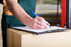 Man's hand signing delivery document Royalty Free Stock Images