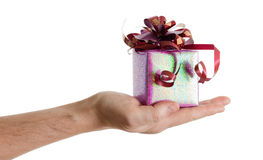 Man's hand with a small red gift box with ribbon Royalty Free Stock Photo