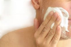 Man`s hand smears shaving foam on his face on white background. royalty free stock photography
