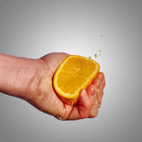 Man's hand squeezes the juice from the orange Stock Photography