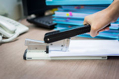 Man's hand stapling paper. On desk Royalty Free Stock Photography