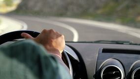 Man`s hand on the steering wheel driving a car in the long road along mountains in slow motion. 3840x2160
