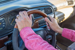Man`s hand on the steering wheel inside of a car.  Stock Photography