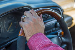 Man`s hand on the steering wheel inside of a car.  Royalty Free Stock Photo