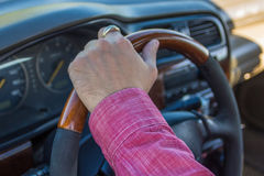 Man`s hand on the steering wheel inside of a car Stock Photo