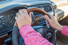 Man`s hand on the steering wheel inside of a car.  Stock Photos