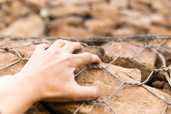 Man`s hand on a stone wall Stock Photography