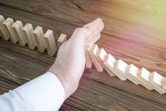 The man`s hand stops the domino effect. Business. volitional decision Royalty Free Stock Image