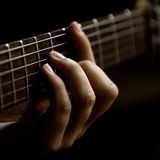A man's hand on the strings of the guitar. The hand of man playing guitar closeup Royalty Free Stock Images