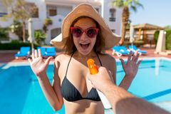 Man`s hand is suddenly applying suntan lotion on surprised woman`s breast on summer vacation at the swiming pool royalty free stock images