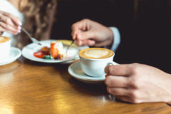 Man`s hand in a suit holding a cup of coffee. Wodden table. selective focus Stock Photo
