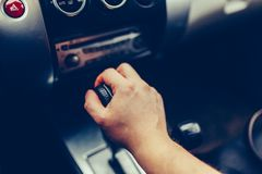 Man's hand switches automatic transmission closeup. Close up view of gear lever manual transmission car interior parts. Stylish T. Oned Photohand shifting an stock photo