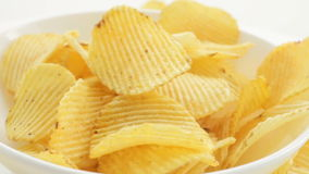 A man's hand takes the chips from a bowl, Rotate Unhealthy Harmful food, yellow delicious Potato ribbed crispy chips stock footage