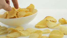 A man's hand takes the chips from a bowl, Unhealthy Harmful food, yellow delicious Potato ribbed crispy chips randomly lying stock video
