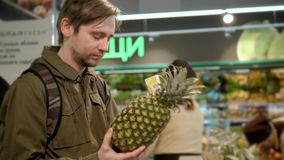 Man`s hand takes a fresh pineapple from the food shelf. Organic products. Vegetables and fruits. Healthy food. Shopping stock footage