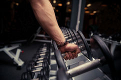 Man's hand takes a heavy dumbbell in gym Stock Photography