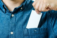 Man`s hand takes out blank business card from the pocket Stock Image
