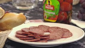 Man's hand takes salami from white big plate on a served table stock footage