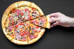 Man`s hand takes slice of freshly baked pizza, top view. Overhead, from above. Close-up. royalty free stock image