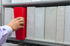 Man& x27;s hand taking off the shelf red folder with documents. Man& x27;s hand taking off the shelf red folder with documents archive file stock photo Stock Photos