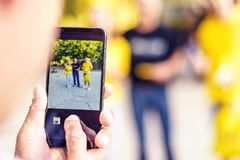 Man`s hand taking a picture of friends on mobile phone Stock Photos